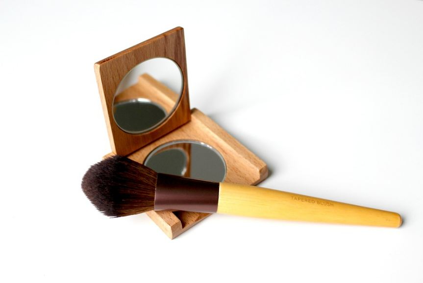 a wooden compact mirror with a makeup brush