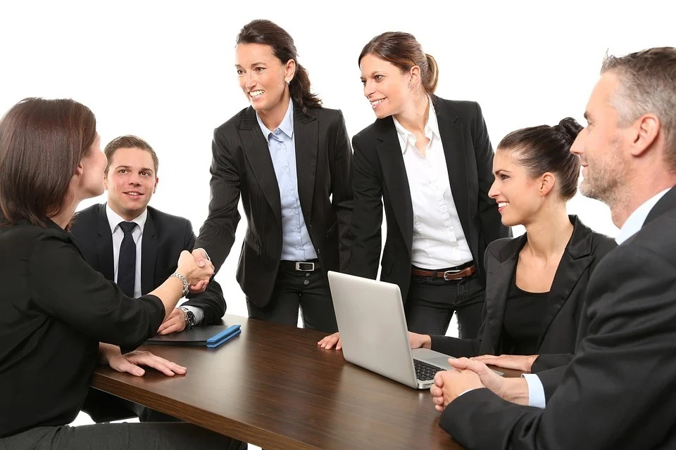 A lady shaking hands in a professional meeting